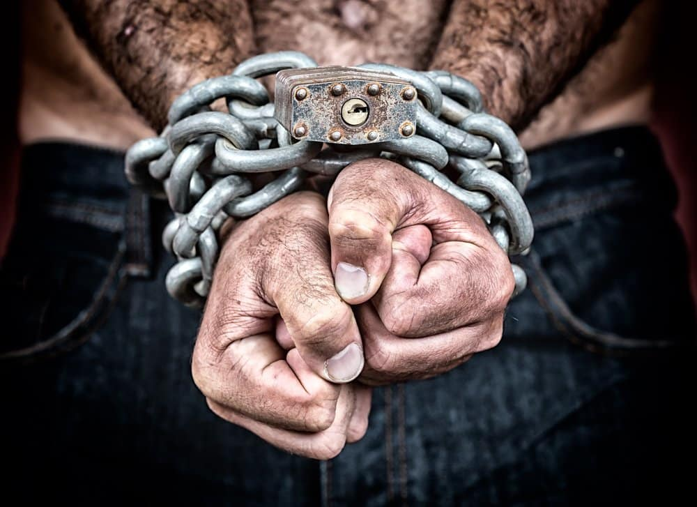 Detail of the chained hands of an adult man