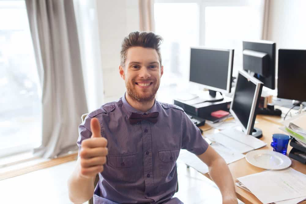 happy male office worker showing thumbs up