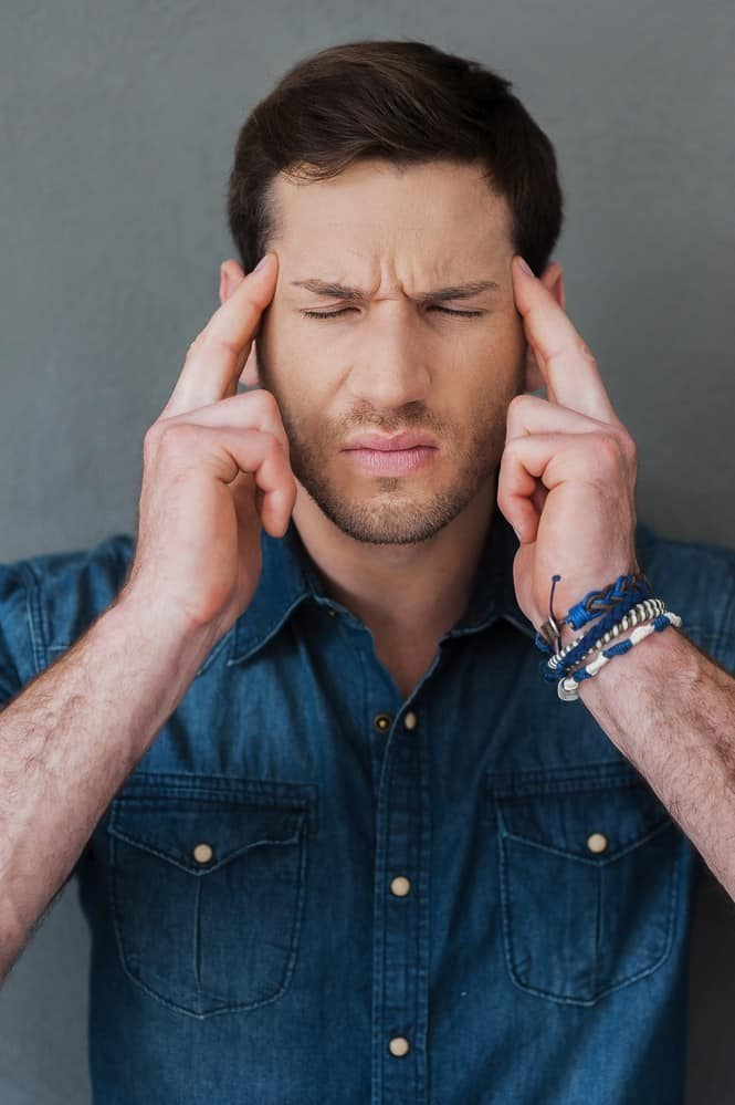 Feeling exhausted. Frustrated young man touching his head while standing against grey background