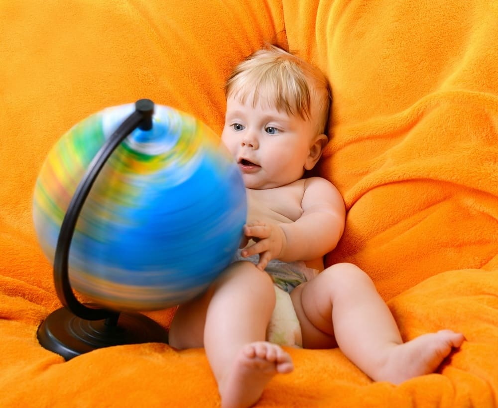 Happy smiling baby boy playing with terrestrial globe sitting on