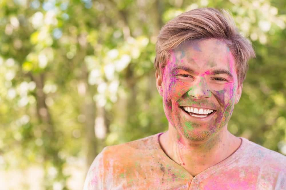 Happy man covered in powder paint on a sunny day
