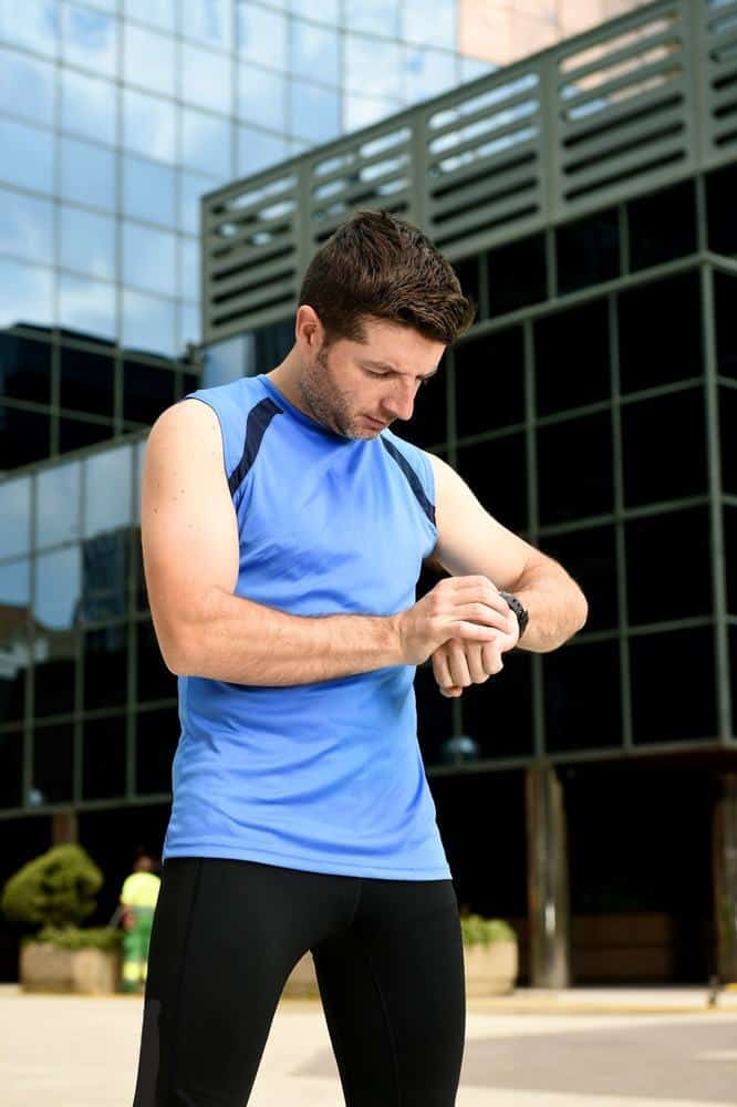 young sport man checking time on chrono timer runners watch holding water bottle after training session